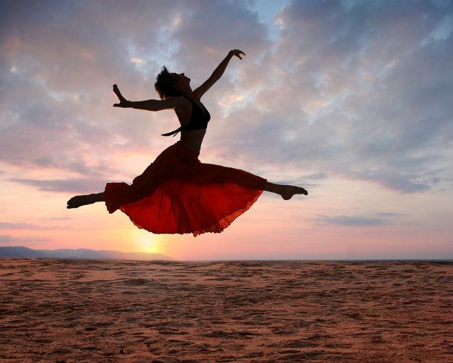 Dramatic image of a woman jumping above the ocean at sunset, silhouette