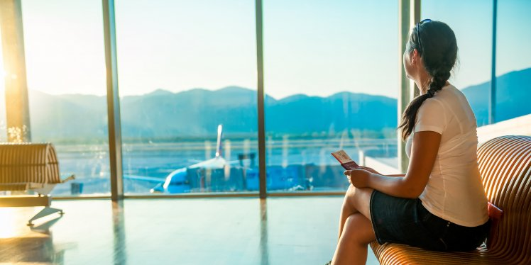 woman-sat-in-airport-lounge-waiting-for-plane-1